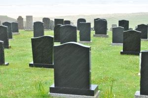 black headstones in rain on graveyard bad weather